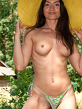 Julie loves the feel of the warm sun on her hairy beaver. See her have some alone time in her big hat and sexy dress out in the long grass.