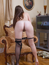 Flora is a sexy brunette who is wearing a bright red dress with black stockings on. Then she seductively strips out of her dress and stockings until she is naked showing off her hairy pussy.