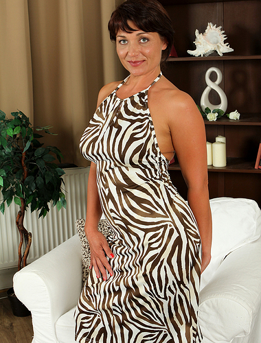 Curvy 38 years old Belle P slides away from her elegant dress to spread