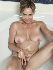 Sarah Michaels stands ready to take a bath and removes her purple robe. She slides into the warm water, and washes up her hairy pussy. After cleaning up, she plays around in the water, and puts on a show.