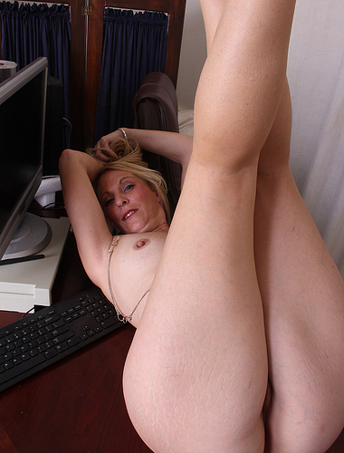 Blonde secretary Jackie stays late at the office to strip and play